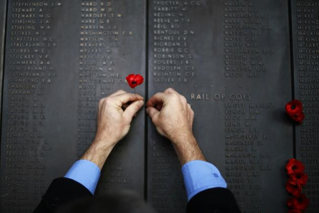 A man places a poppy flower into the World War I Wall of Remembrance on ANZAC Day at the Australian National War Memorial in Canberra