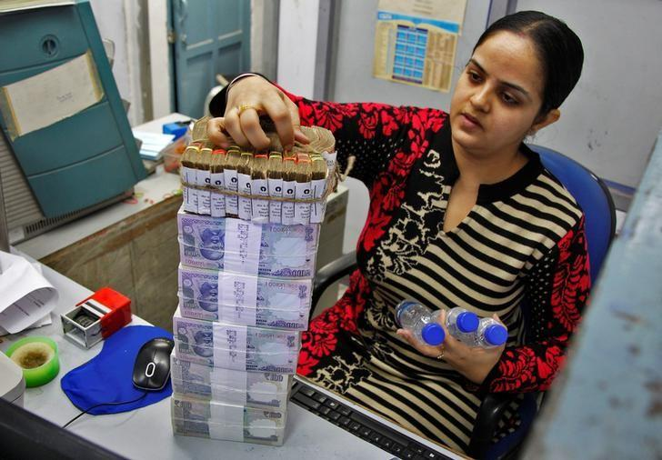 A cashier stacks Indian currency notes inside a bank in Chandigarh
