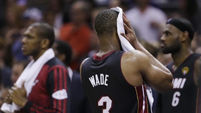 Miami Heat guard Dwyane Wade (3) wipes his face in the final moments at Game 5 of the NBA basketball finals on Sunday, June 15, 2014, in San Antonio. The San Antonio Spurs won the NBA championship 104-87
