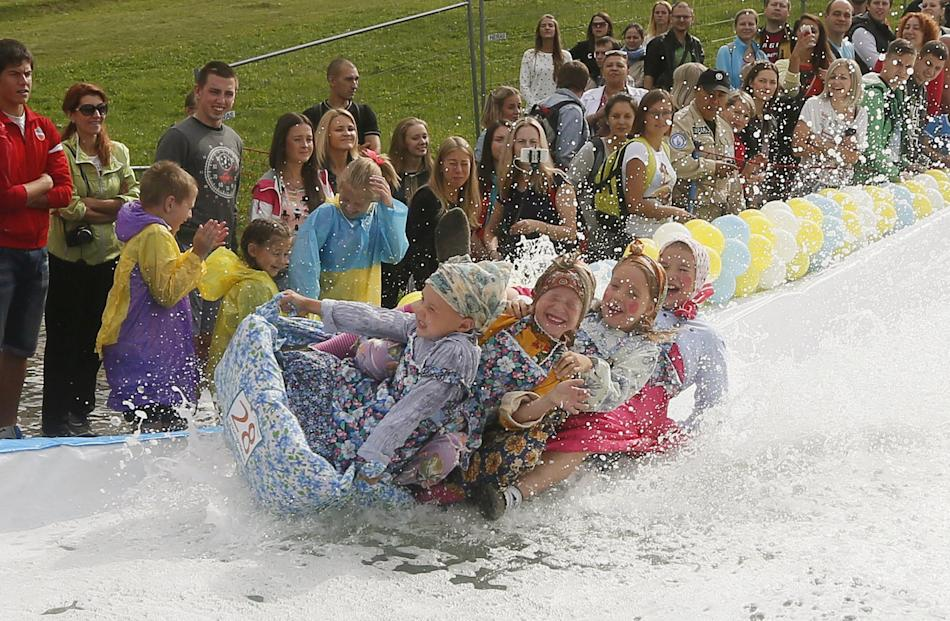 Children slide down along a chute to cross a pool of water and foam during a festival near Krasnoyarsk