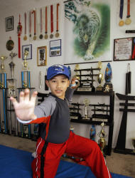 FILE - In this May 2, 2008 file photo, Moshe Kai Cavalin, 10, strikes a martial arts position as he poses for photos at his home studio in Downey, Calif. At age 11, Cavalin became the youngest person ever to earn an Associate in Arts degree from East Los Angeles College and now, at 14, is poised to graduate with honors from UCLA later this year. (AP Photo/Damian Dovarganes, File)