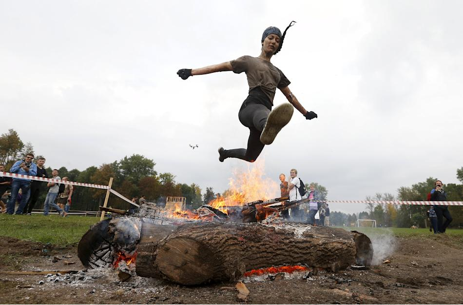 Woman jumps over the fire as she takes part in an extreme run ...