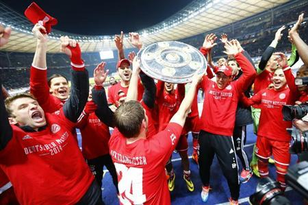 Bayern Munich players celebrate with mock-up German soccer championships trophy after their German first division Bundesliga soccer match against Hertha Berlin in Berlin March 25, 2014. REUTERS/Kai Pfaffenbach