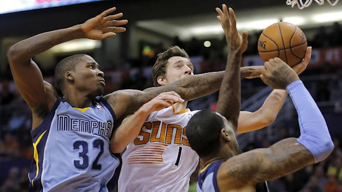 Phoenix Suns' Goran Dragic (1), of Slovenia, drives against Memphis Grizzlies' Ed Davis (32) and James Johnson during the second half of an NBA basketball game on Thursday, Jan. 2, 2014, in Phoenix. The Grizzlies won 99-91
