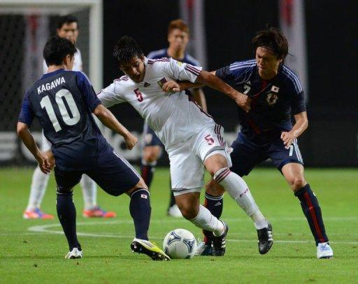 Venezuela's Francisco Flores (C) fights the ball against Japan's Yasuhito Endo (R) and Shinji Kagawa