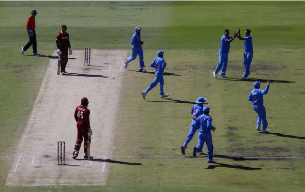 West Indies batsmen Samuels stands at his crease as India's team celebrates his being run out  as his teammate Gayle watches during their Cricket World Cup match in Perth