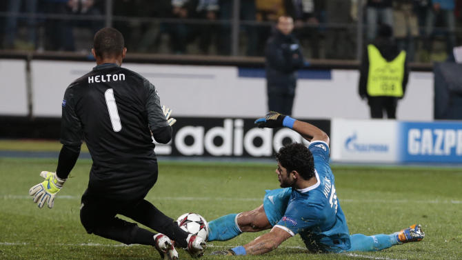 Zenit's Hulk, right. shoots at goal as Porto's goalkeeper Helton closes in to block during the Champions League group G soccer match between Zenit and Porto at Petrovsky stadium in St.Petersburg, Russia, on Wednesday, Nov. 6, 2013