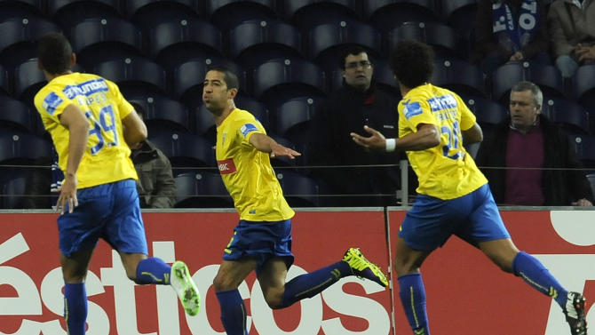Estoril's Evandro Goebel, centre, celebrates with Bruno Lopes, both from Brazil, and Carlitos Garcia, right, after scoring a penalty goal against FC Porto in a Portuguese League soccer match at the Dragao stadium, in Porto, Portugal, Sunday, Feb. 23, 2014. Porto lost 1-0