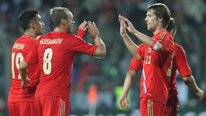 Russia's Denis Glushakov, second left, gets congratulations by his team mates, after he scored, during the World Cup 2014 Group F qualifying soccer match against Luxembourg, in Luxembourg city, at the Josy Barthel stadium, Friday, Oct. 11, 2013