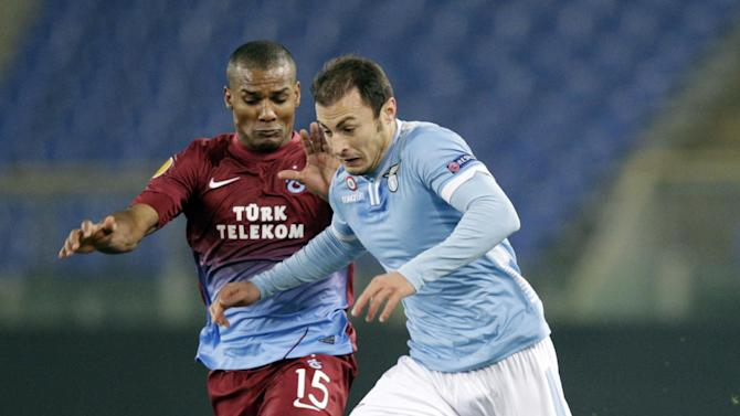 Trabzonspor midfielder Florent Malouda, left, and Lazio defender Stefan Radu, of Romania, fight for the ball during an Europa League Group J soccer match, at Rome's Olympic stadium, Thursday, Dec. 12, 2013