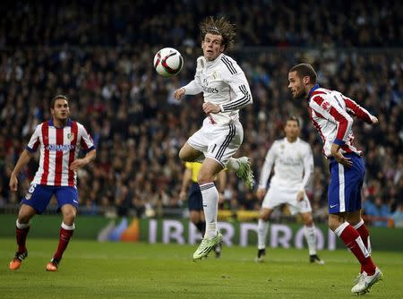 Real Madrid?s Gareth Bale heads the ball challenged by Atletico Madrid?s Mario Suarez during their King's Cup round of 16 second leg soccer match in Madrid