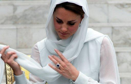 "Catherine, the Duchess of Cambridge, wife of Britain's Prince William, adjusts her scarf outside a mosque in Kuala Lumpur on September 14, on the second leg of a nine-day Southeast Asian and Pacific tour. The British royal family have warned an Italian magazine that ""unjustifiable upset"" would be heaped on Catherine if it went ahead and printed topless photos of her."