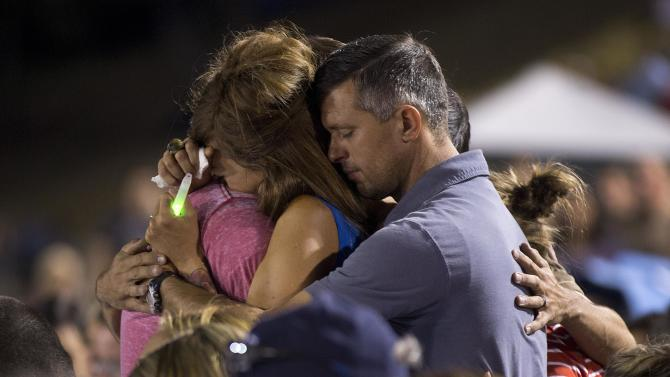 Juliann Ashcraft, left, wife of Granite Mountain Hotshot firefighter Andrew Ashcraft, hugs members of her family during a candlelight vigil, Tuesday, July 2, 2013 in Prescott, Ariz. Andrew Ashcraft was one of 19 members of the crew that was killed by an out-of-control blaze near Yarnell, Ariz. on Sunday. (AP Photo/Julie Jacobson)