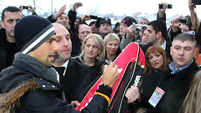 Tennis world number one Novak Djokovic signs autographs for fans on February 9, 2012, in the central Serbian town of Jagodina.  Novak Djokovic attended a ceremony reviling his wax sculpture in the Wax museum in central Serbian town Jagodina. Djokovic returned to Serbia, where he is considered a national hero, after winning the Australian Open in the longest finals in the history of this tournament against Rafael Nadal.   AFP PHOTO / SASA DJORDJEVIC (Photo credit should read SASA DJORDJEVIC/AFP/Getty Images)