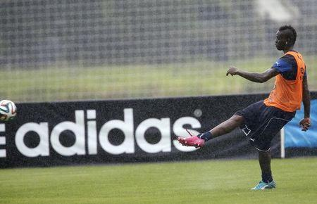 Italy's national soccer player Balotelli kicks the ball as an Adidas advertising banner is seen during a training session ahead of the 2014 World Cup in Mangaratiba