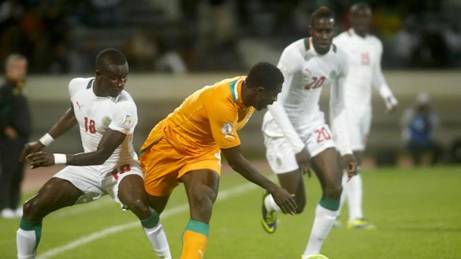 Ivory Coast's Toure Kolo Abib, center, is challenged by Senegal's Souare Pape Ndiaye, and Sane Salif, right, during their World Cup Group H qualifying soccer match at Mohammed V stadium in Casablanca, Morocco, Saturday Nov. 16, 2013. Ivory Coast qualified for the World Cup tournament by beating Senegal 4-2 on aggregate in a playoff for next year's finals in Brazil after a 1-1 draw