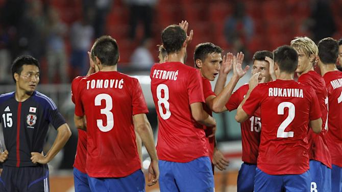 Serbian soccer players celebrate after the farewell match of retiring Serbian  soccer player Dejan Stankovic, against Japan, at Karadjordje stadium in Novi Sad, Serbia, Friday, Oct. 11, 2013. Stankovic has played for Red Star Belgrade (1994-1998), Lazio (1998-2004) and Inter Milan (2004-2013). After this match Stankovic will have the largest number of appearances in Serbian national team history