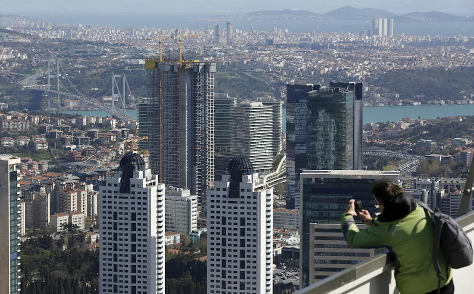 A visitor takes pictures of the Levent district, which comprises of leading Turkish companies' headquarters and popular shopping malls, in Istanbul