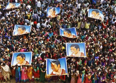 School children wave as they hold posters of Indian cricketer Sachin Tendulkar at an event to honour him in Chennai