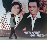 This file photo shows a large picture of former South Korean president Park Chung-Hee and his wife, displayed outside a state hall in Seoul, in 1999, before a photo exhibit commemorating the late dictator. Park is credited with laying the foundations for S.Korea's economic rise, and admirers say his autocratic style was justified by the poverty, security issues and social divisions existing then