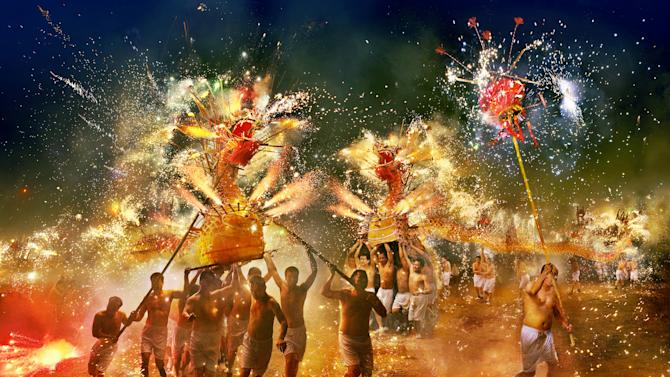 "'Arts and Culture' winner: Gilbert Yu, Hong Kong. 'Fire Dragon of ""Fung Shun""' was taken to document the annual ceremony 15 days after the start of Lunar New Year. The 'Fung Shun' fire dragon dance sees strong men carry the dragons while fireworks attached to the model are lit (Gilbert Yu, Hong Kong, Winner, Arts and Culure, Open Competition, 2013 Sony World Photography Awards)"