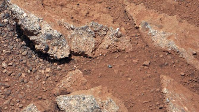 This image provided by NASA shows shows a Martian rock outcrop near the landing site of the rover Curiosity thought to be the site of an ancient streambed. Curiosity landed in a crater near Mars' equator on Aug. 5, 2012, on a two-year mission to study whether the environment could have been favorable for microbial life. (AP Photo/NASA)