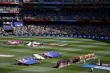 Australian and New Zealand players stand together as they play the national anthems before the start of their Cricket World Cup final match at the MCG