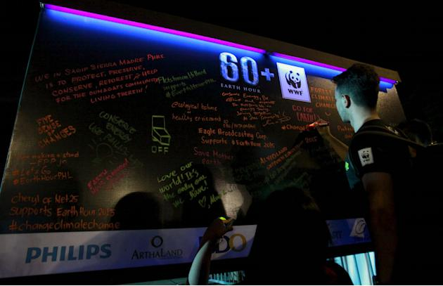 Participants write their pledges on a board during Earth Hour in Quezon city, metro Manila