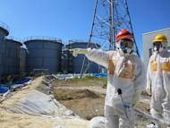 This handout picture taken by Tokyo Electric Power Co. (TEPCO) on August 26, 2013 and received on September 1, 2013 shows Japanese Economy, Trade and Industry Minister Toshimitsu Motegi (red helmet) at TEPCO's Fukushima Dai-ichi nuclear power plant. Prosecutors on Monday decided not to charge former prime minister Naoto Kan and TEPCO bosses over the initial stages of the disaster