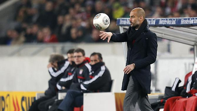 Bayern head coach Pep Guardiola of Spain carries a ball during a German first soccer division Bundesliga match between VfB Stuttgart and FC Bayern Munich in Stuttgart, Germany, Wednesday, Jan. 29, 2014