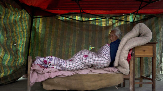 An elderly woman rests on a makeshift bed setup outdoors near Shangli town in southwestern China's  Sichuan province, Sunday, April 21, 2013. Residents awoke Sunday after spending the night outdoors or in their cars in a town near the epicenter of a powerful earthquake that struck the steep hills of China's southwestern Sichuan province, leaving at least 160 people dead and more than 6,700 injured. (AP Photo/Ng Han Guan)