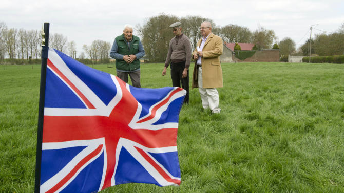 In this photo taken on Monday, April 22, 2013, farmer Didier Guerle, center, writer Philippe Duhamel, right, and amateur archeologist and historian Moise Dilly, left, stand near a British flag which marks an area in a field in which they located the bodies of two British World War I soldiers in 2009 in Bullecourt, France. Almost 100 years after they were killed in action, Lt. John Harold Pritchard and Pvt. Christopher Douglas Elphick will be re-interred with full military honors in the H.A.C Cemetery at Ecoust-St. Mein, France, on Tuesday, April 23, 2013. (AP Photo/Virginia Mayo)