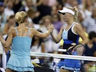 Caroline Wozniacki of Denmark (R) shakes hands with Camila Giorgi of Italy after losing her match to Giorgi at the U.S. Open tennis championships in New York August 31, 2013. REUTERS/Adam Hunger