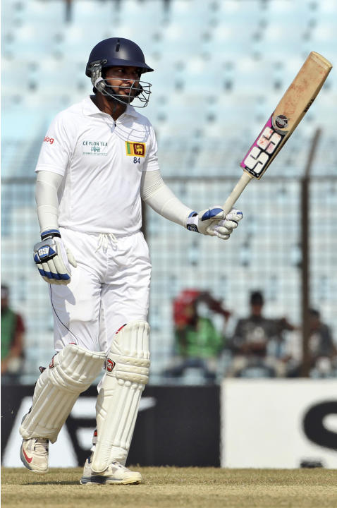 Sri Lanka's Kumar Sangakkara acknowledges the crowd after scoring a century on the fourth day of the second test cricket match against Bangladesh in Chittagong, Bangladesh, Friday, Feb. 7, 2014. (