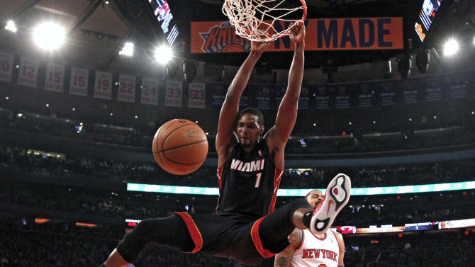 Miami Heat's Chris Bosh (1) dunks the ball ahead of New York Knicks' Tyson Chandler (6) during the first half of an NBA basketball game Saturday, Feb. 1, 2014, in New York. (AP Photo/Jason DeCrow)