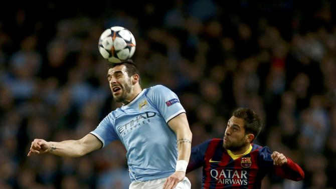 Manchester City's Alvaro Negredo is challenged by Barcelona's Jordi Alba during their Champions League round of 16 first leg soccer match at the Etihad Stadium in Manchester