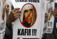 "A Muslim woman holds a poster bearing a defaced picture of U.S. pop singer Lady Gaga during a protest against her concert that is scheduled to be held on June 3, in Jakarta, Indonesia, Thursday, May 24, 2012. Lady Gaga might have to cancel her sold-out show in Indonesia because police worry her sexy clothes and dance moves undermine Islamic values and will corrupt the country's youth. The writing on the poster reads ""Infidel."" (AP Photo/Tatan Syuflana)"
