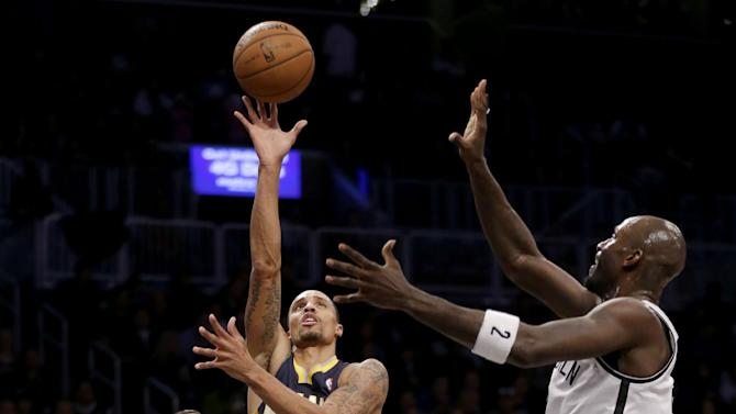 Indiana Pacers' George Hill, center, puts up a shot between Brooklyn Nets' Deron Williams, left, and Kevin Garnett during the first half of an NBA basketball game Monday, Dec. 23, 2013, in New York