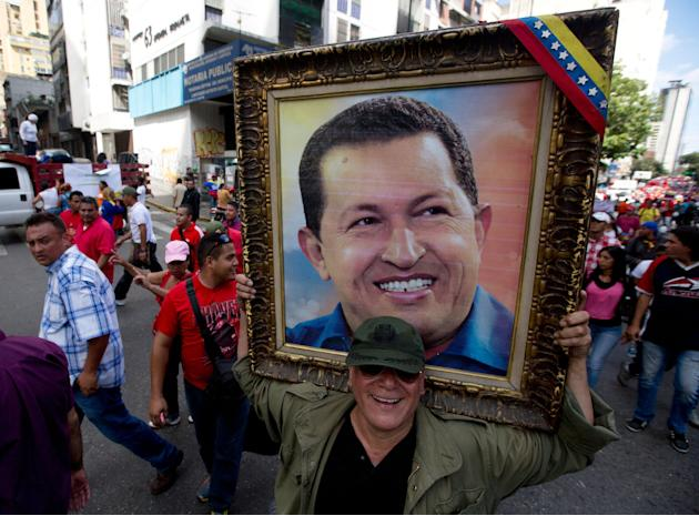 In this Feb. 28, 2015 photo, a man holds a framed image of the late President Hugo Chavez during a pro-government rally outside of the Miraflores presidential palace in Caracas, Venezuela. Venezuelans