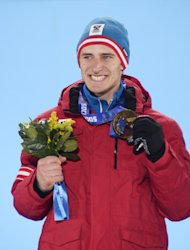 Austria's gold medalist Matthias Mayer poses with his medal on the podium during the Men's Alpine Skiing Downhill Medal Ceremony at the Sochi medals plaza during the Sochi Winter Olympics on February 9, 2014
