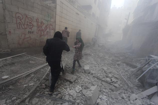Residents walk amid rubble of collapsed buildings after what activists said were air strikes by forces loyal to Syria's President Bashar al-Assad in Douma Eastern Al-Ghouta, near Damascus