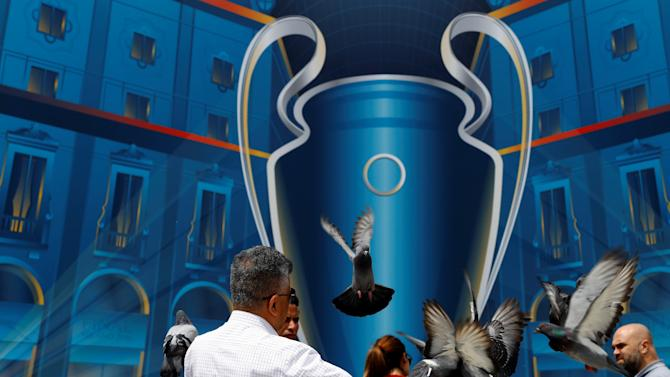 A man feeds pigeons in front of the Champions League poster at the Duomo square in Milan