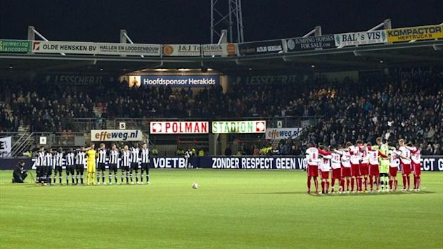 Heracles Almelo and FC Utrecht players observe a minute of silence before their game in memory of linesmen Richard Nieuwenhuizen (AFP)