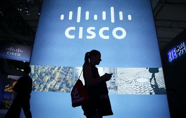 A visitor walks past a Cisco advertising panel as she looks at her mobile phone at the Mobile World Congress in Barcelona February 27, 2014. REUTERS/Albert Gea (SPAIN - Tags: BUSINESS TELECOMS SCIENCE TECHNOLOGY)