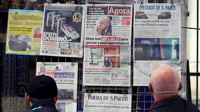 People read the local newspaper front pages showing pictures of FIFA's Sepp Blatter in Sao Paulo