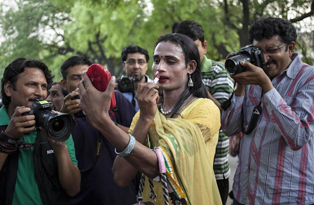 Photographers gather around an transgender Indian applying lipstick during a gathering to celebrate Tuesday's landmark verdict recognizing transgender rights as human rights, saying people can identif