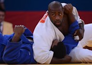 France's Teddy Riner (white) competes with Cuba's Oscar Brayson (blue) during their men's +100kg judo contest quarter final match of the London 2012 Olympic Games on August 3, 2012 at the ExCel arena in London. AFP PHOTO / EMMANUEL DUNAND