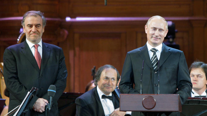 FILE- In this June 14, 2011, file photo, then-Russian Prime Minister Vladimir Putin, right, and Artistic Director of the Mariinsky Theater, conductor Valery Gergiev, left, are at the opening ceremony of the 14th International Tchaikovsky Competition in the Big Hall of the Moscow Conservatory in Moscow, Russia. An artists' spat over President Vladimir Putin and his adoption ban joins a long tradition in Russian politics. At the core of the argument today is a question about what an artist's role should be in Putin's Russia: attracting generous state funding for bigger and better artistic projects, or challenging the political system in a way most ordinary citizens cannot afford to do.  (AP Photo/RIA Novosti, Yana Lapikova, Pool, File)