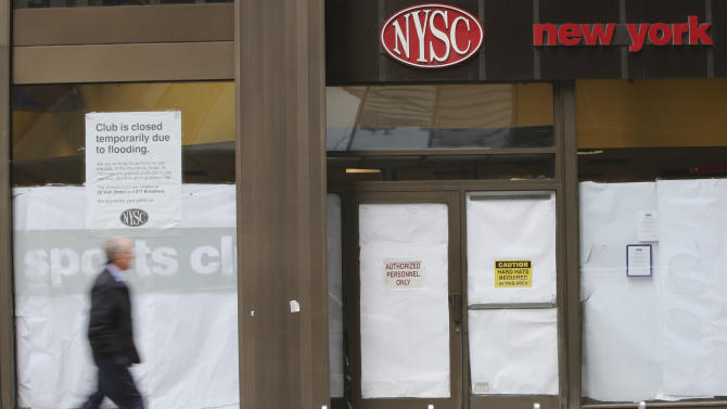 In this Thursday, Feb. 7, 2013 photo, a pedestrian walks past the shuttered New York Sports Club on Water St. in New York. Nearly four months after Superstorm Sandy hit, the historic cobblestone streets near the water's edge in lower Manhattan are eerily deserted, and among local business owners, there is a pervasive sense that their plight has been ignored by the rest of Manhattan. (AP Photo/Mary Altaffer)