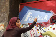 "FILE - In this March 30, 2011, file photo. an art student from the University of Helwan paints the Facebook logo on a mural commemorating the revolution that overthrew Hosni Mubarak in the Zamalek neighborhood of Cairo, Egypt. The team from the CIA's Open Source Center, housed in a unassuming brick building in a Virginia industrial park, pores daily over tweets, Facebook, newspapers, TV news channels, local radio stations, Internet chat rooms _ anything overseas that anyone can access, and contribute to, openly. The center saw the uprising in Egypt coming said the center's director, Doug Naquin. The center already had ""predicted that social media in places like Egypt could be a game-changer and a threat to the regime,"" he said in a recent interview with The Associated Press. (AP Photo/Manoocher Deghati, File)"